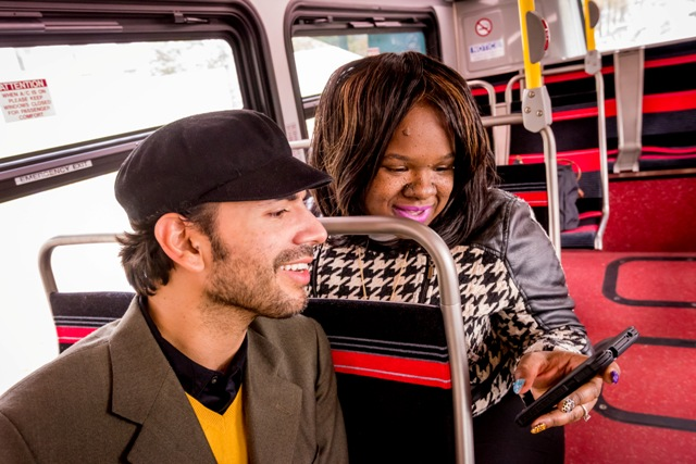 Two folks on bus looking at phone